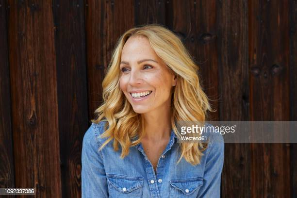 happy blond woman in front of wooden wall - attraktive frau stock-fotos und bilder