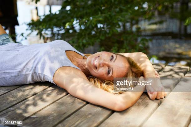happy blond woman lying on wooden jetty at a lake - one mature woman only stock pictures, royalty-free photos & images
