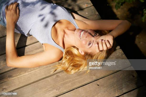 happy blond woman lying on wooden jetty in sunshine - einzelne frau über 40 stock-fotos und bilder