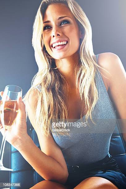 happy blond woman sitting with a glass of champagne - women wearing short skirts stock pictures, royalty-free photos & images