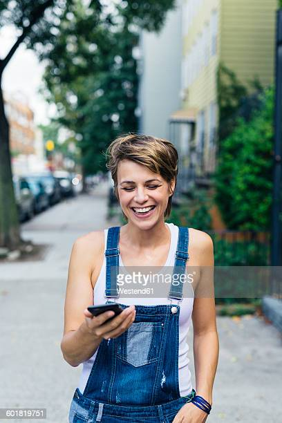 Happy blond woman wearing jeans dungarees with smartphone