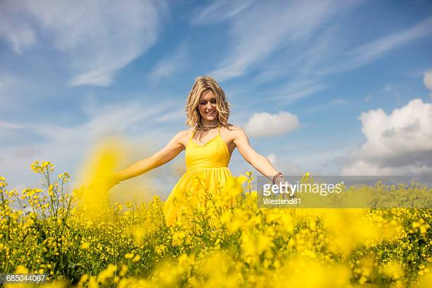 happy blond woman wearing yellow dress standing in rape field - yellow dress stock pictures, royalty-free photos & images