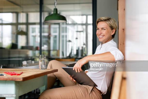 happy blond woman with tablet sitting at table - une seule femme d'âge moyen photos et images de collection