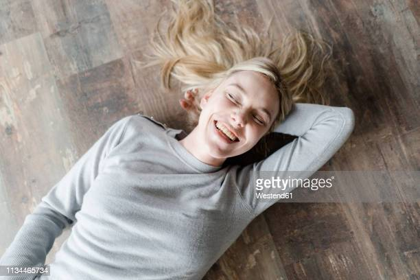 happy blond young woman lying on wooden floor - lying down stock pictures, royalty-free photos & images