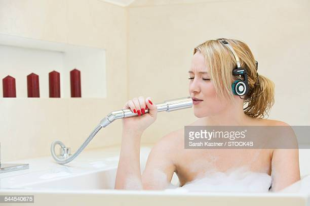 Happy blond young woman singing in bathtub