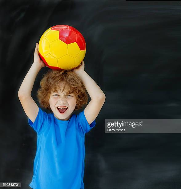 happy blonde boy holding a  ball over his head