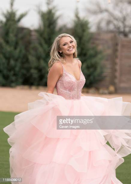 happy blonde in pink dress twirling. - prom dress stock pictures, royalty-free photos & images