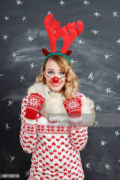 happy blonde woman in winter outfit and reindeer antlers headband - clown's nose stock photos and pictures