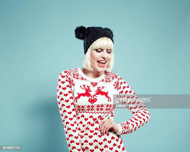 Happy blonde young woman wearing xmas sweater and bobble hat