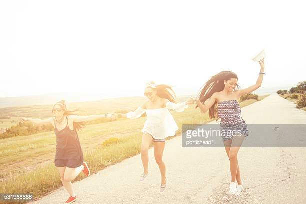 Happy boho women holding hands and dancing on the road