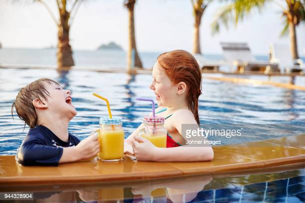 happy boy and girl in swimming-pool - very young thai girls stock photos and pictures