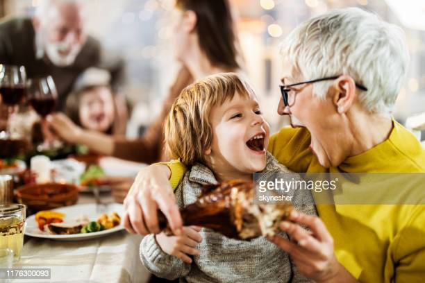 happy boy and his grandmother about to eat turkey leg at dining table. - thanksgiving holiday stock pictures, royalty-free photos & images