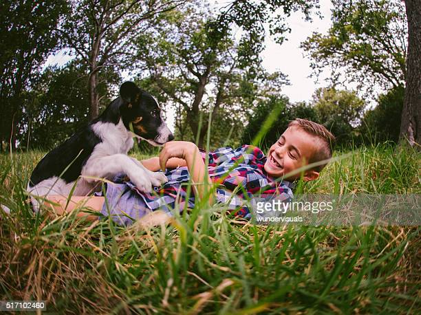 Happy boy and his puppy dog frolicking around in grass