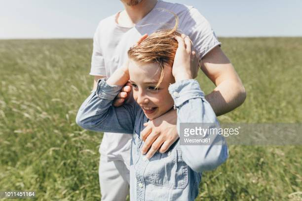 happy boy and young man in a field - beschützer stock-fotos und bilder