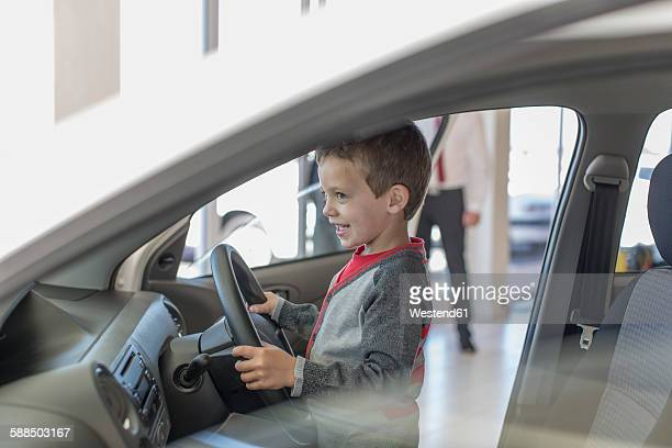 Happy boy at car dealer inside car steering