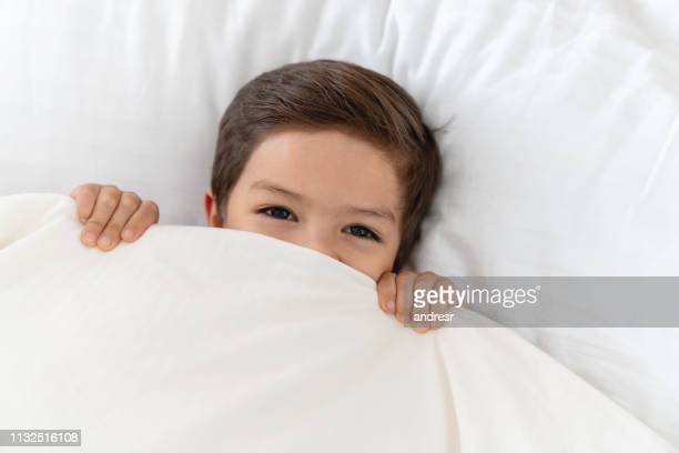 happy boy at home lying in bed under the covers - duvet stock pictures, royalty-free photos & images