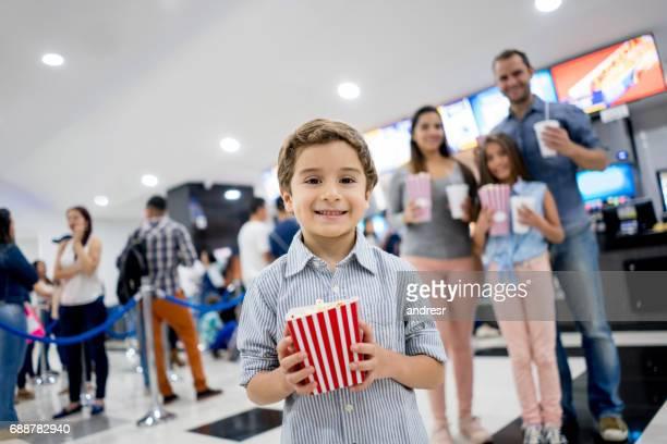Fröhlicher Junge im Kino mit seinen Eltern kaufen popcorn