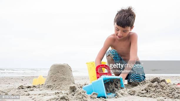 Happy boy builds sand castle