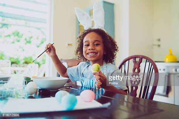 happy boy coloring easter egg at home - african american easter stock photos and pictures