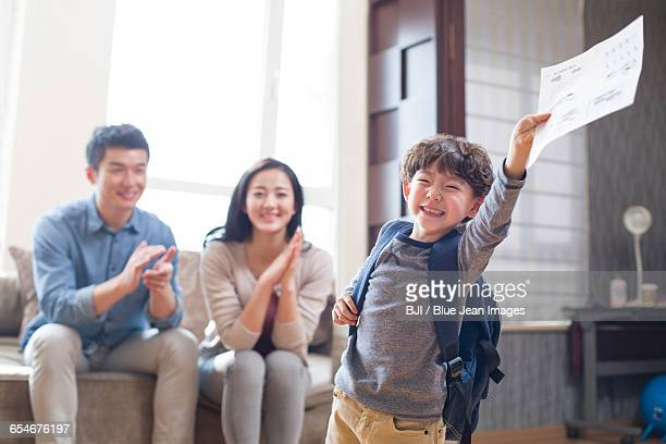 Happy boy coming home from school with a report card