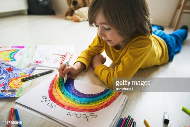 happy boy drawing at home. covid-19 crisis - rainbow stock pictures, royalty-free photos & images