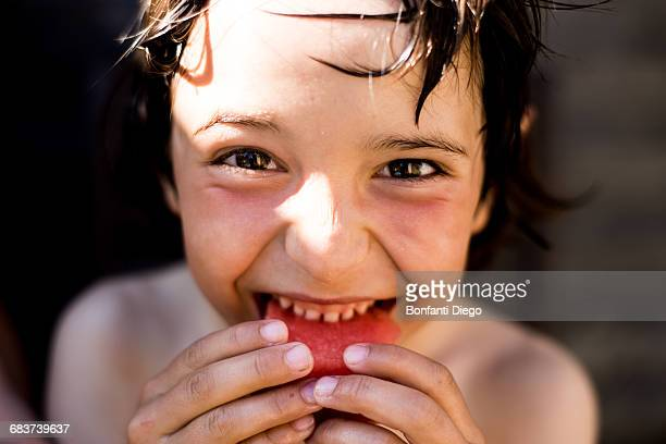 Happy boy eating watermelon on summer day