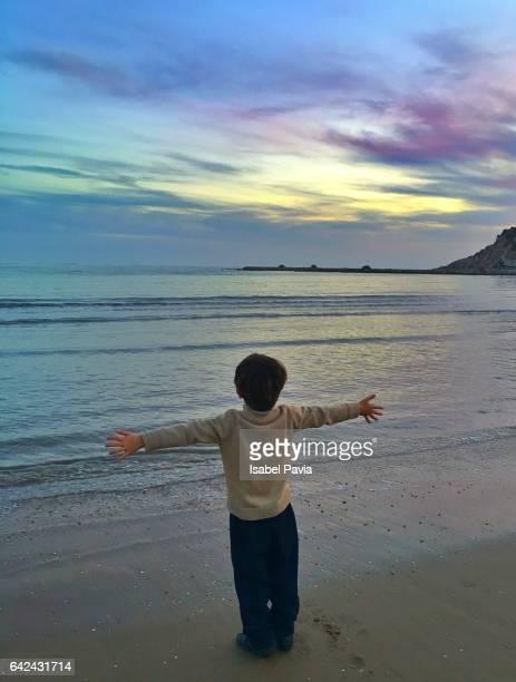 Happy boy enjoying dramatic sky at sunset in Mediterranean sea