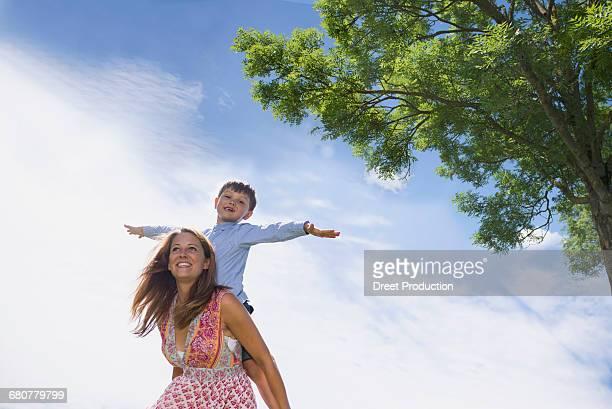 Happy boy enjoying piggyback ride on mother at picnic, Bavaria, Germany