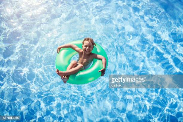 happy boy floating on swim ring in the swimming pool - very young tube stock photos and pictures