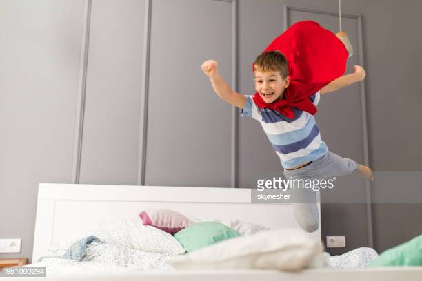 happy boy flying like a superman in a bedroom. - mid air stock pictures, royalty-free photos & images