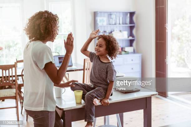 happy boy giving high-five to mother at home - high five stock pictures, royalty-free photos & images