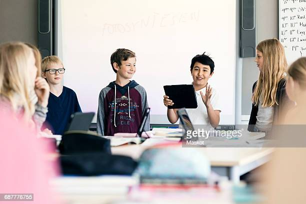 Happy boy giving presentation with digital tablet amidst students in classroom