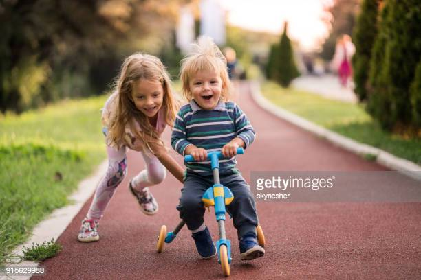 happy boy having fun on tricycle while his sister is pushing him. - sister stock photos and pictures