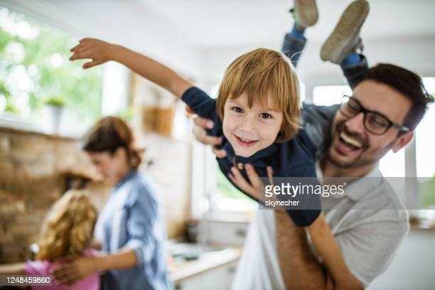 garçon heureux ayant l'amusement avec son père dans la cuisine. - famille photos et images de collection