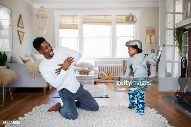 Happy boy hitting father with artificial sword at home