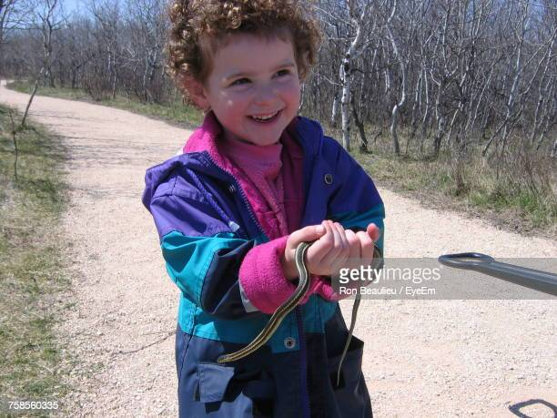 Happy Boy Holding Garter Snake While Standing On Road Amidst Bare Trees