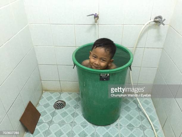 happy boy in bucket in bathroom - boys taking a shower stock pictures, royalty-free photos & images