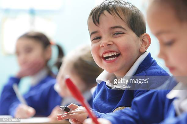 Happy boy in class at school