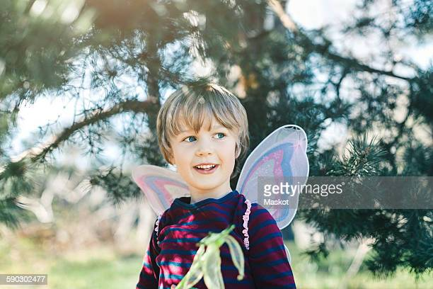 happy boy in fairy wings looking away at yard - fairy stock photos and pictures