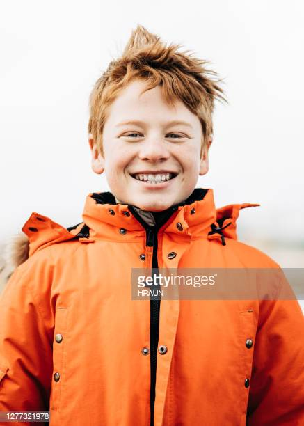 happy boy in warm clothing against sky - coat stock pictures, royalty-free photos & images