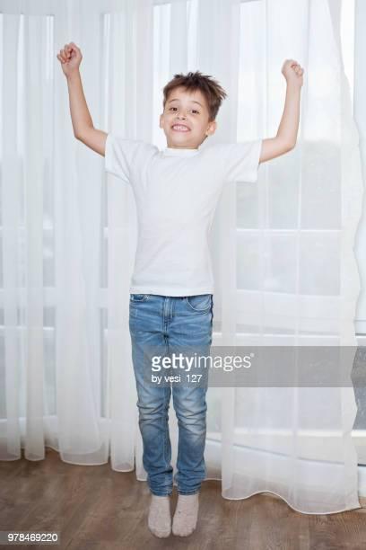 happy boy jumping for joy - 白tシャツ ストックフォトと画像
