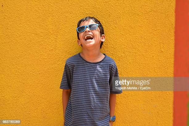 Happy Boy Laughing Against Yellow Wall