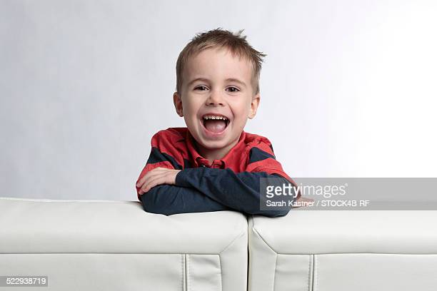 Happy boy leaning on couch