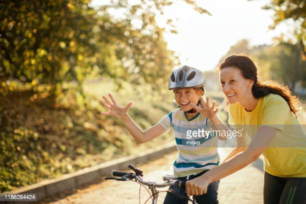 happy boy learning to ride a bicycle in park at sunset - hands free cycling stock pictures, royalty-free photos & images