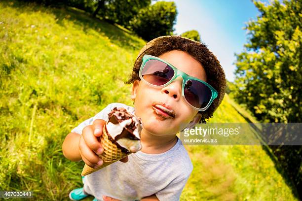 Happy boy licking enjoying ice cream on hot summer day