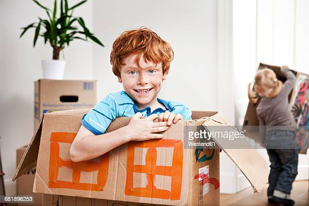 happy boy looking out of a cardboard box in new apartment with sister in background - 6 7 jahre stock-fotos und bilder