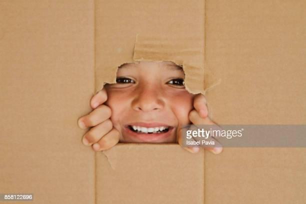 Happy Boy looking through a hole on cardboard