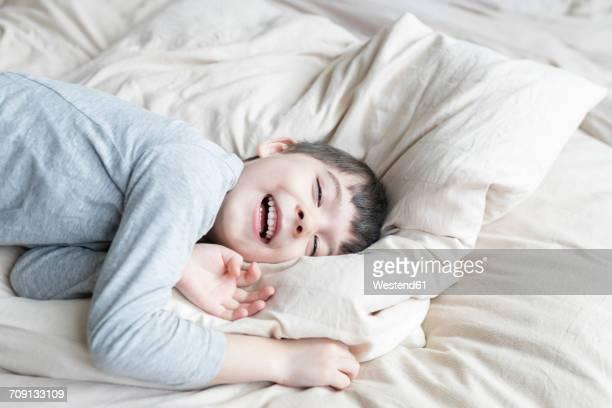Happy boy lying in bed