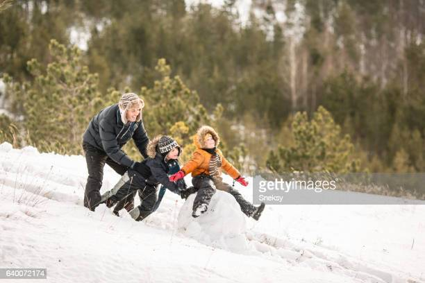 Happy boy making snowman with her family