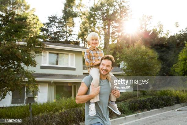 happy boy on father's shoulders in front of their home - middle class stock pictures, royalty-free photos & images